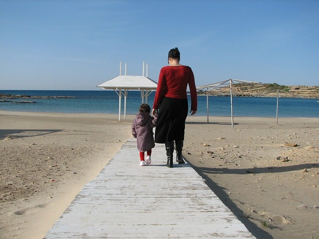 mom and child walking on beach for a mental health day