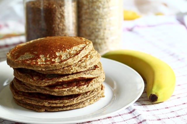 whole wheat pancakes with a banana on a table.