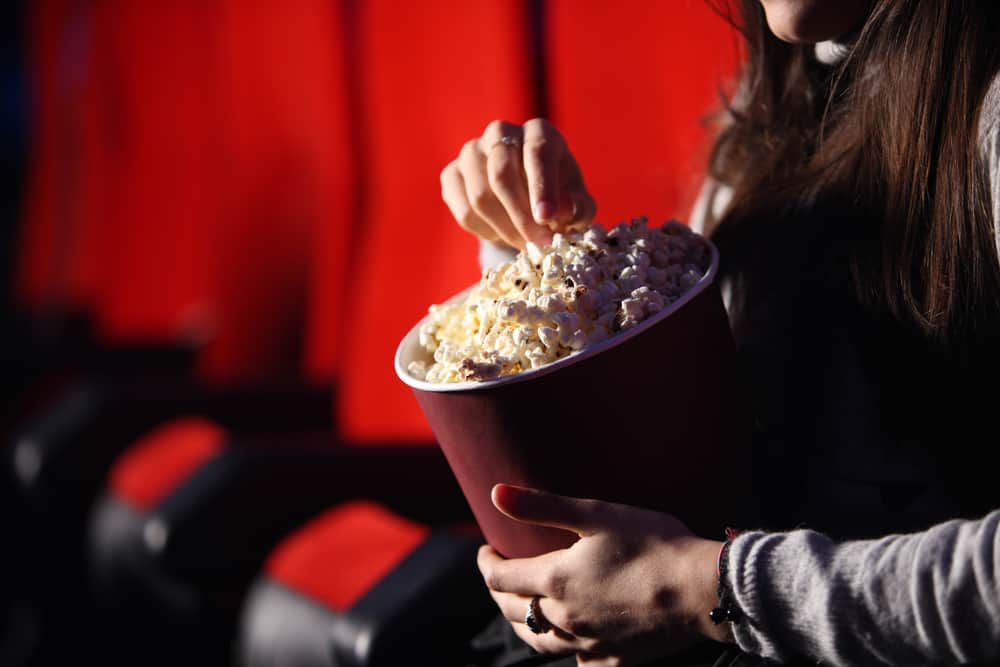 close up of the hands of a girl in a movie theater, she eats popcorn