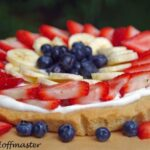 summer fruit tart made with sugar cookie crust, berries, and bananas