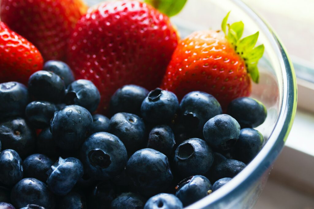 blueberries and strawberries in a glass bowl