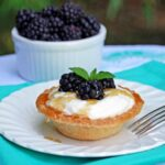 whipped ricotta cheese tart with fresh blackberries on a white plate