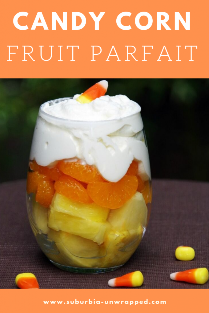 Layers of pineapple and orange slices in a parfait glass topped with whipped cream and candy corn for a healthy Halloween dessert