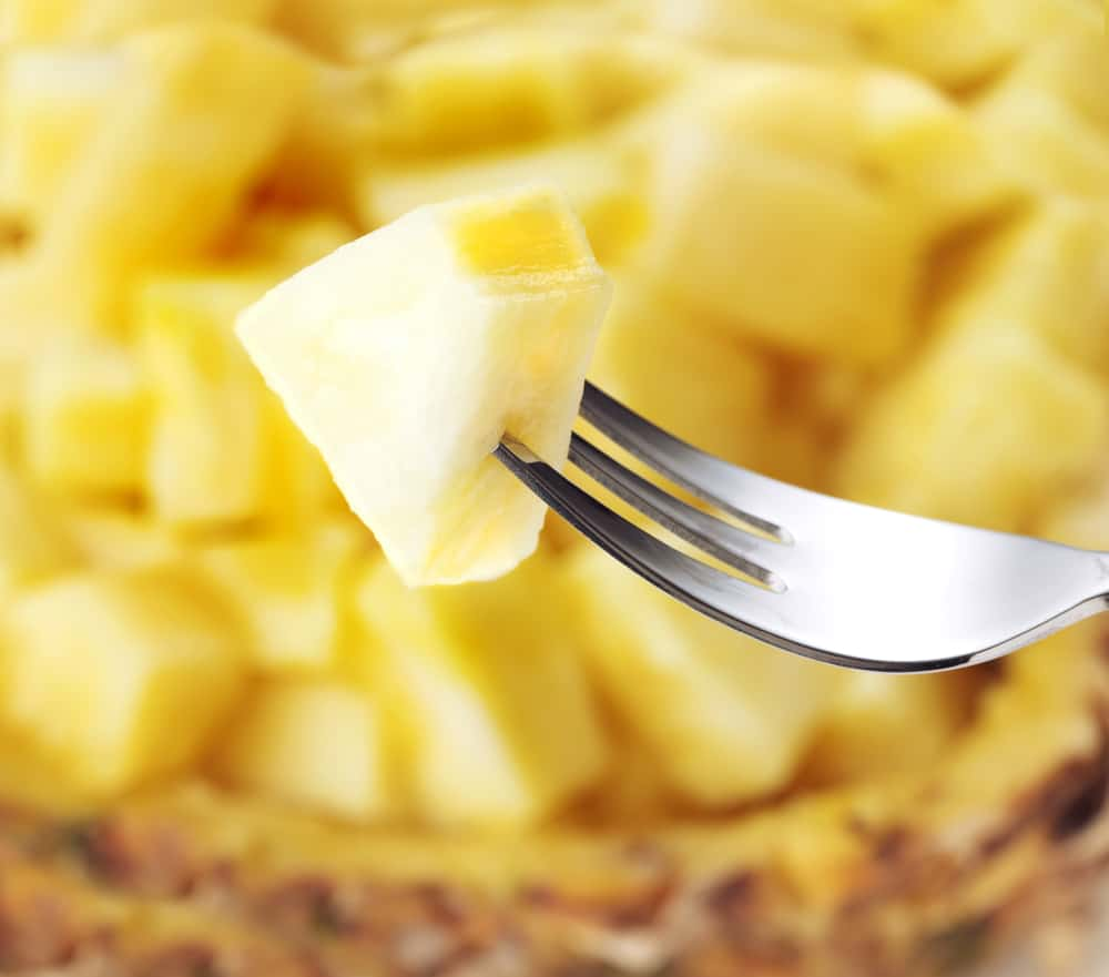 bowl of fresh pineapple with fork holding one piece
