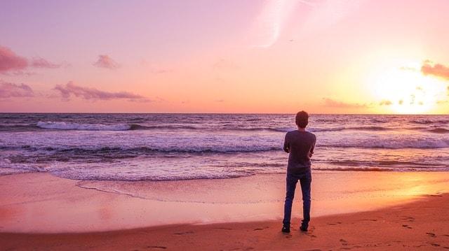 teenage boy standing alone on the beach