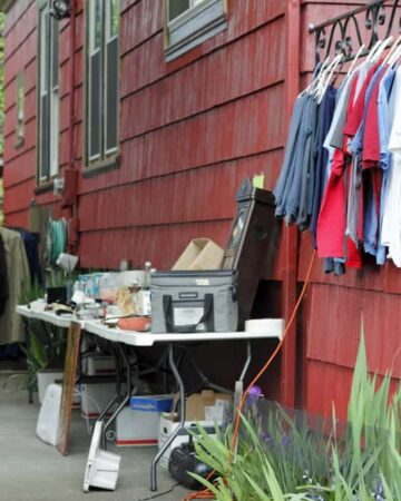 Outdoor yard sale of clothes hanging off the house and fence and many other items on tables in the driveway that has a carport over it.