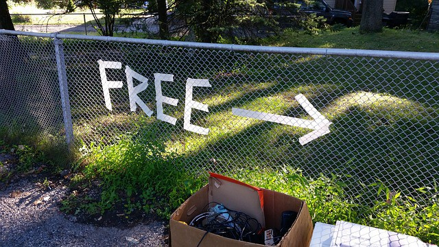 free sign on chain link fence with arrow