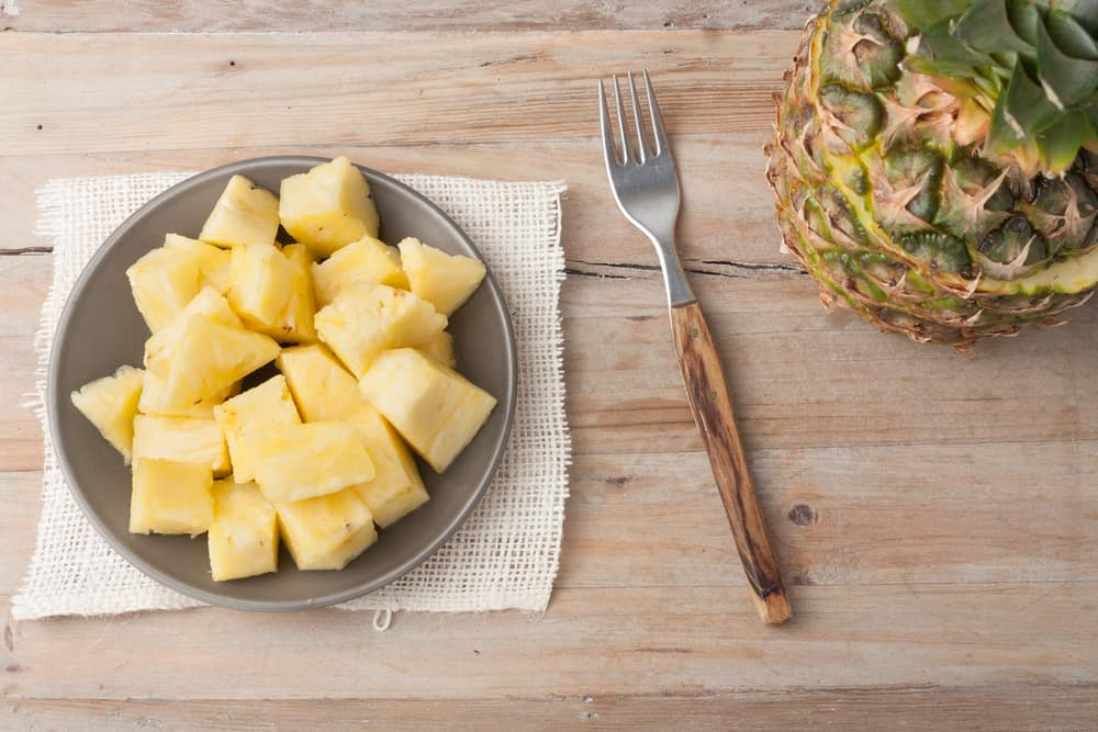 pineapple chunks on a plate on wooden rustic background