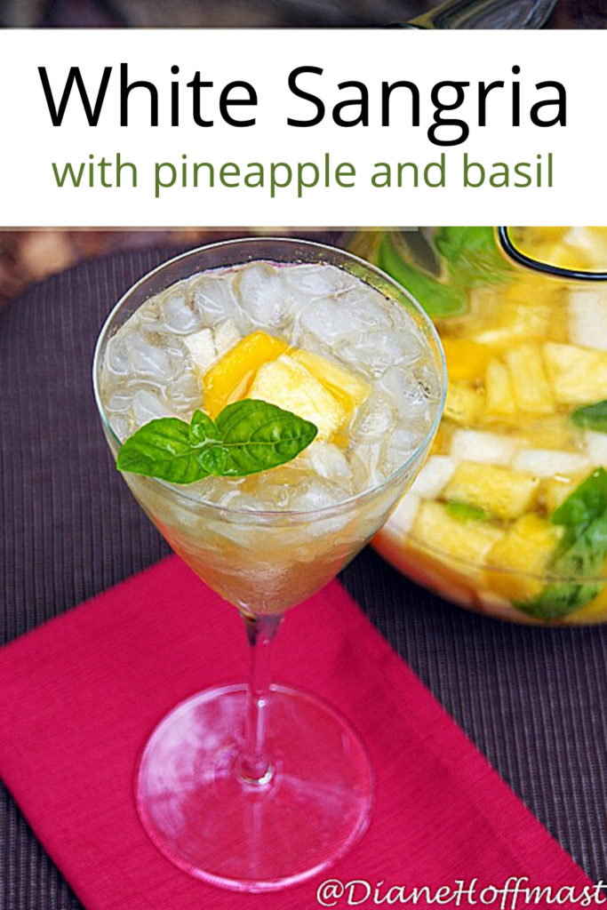 White Sangria with pineapple and basil in a pitcher and long stemmed glass