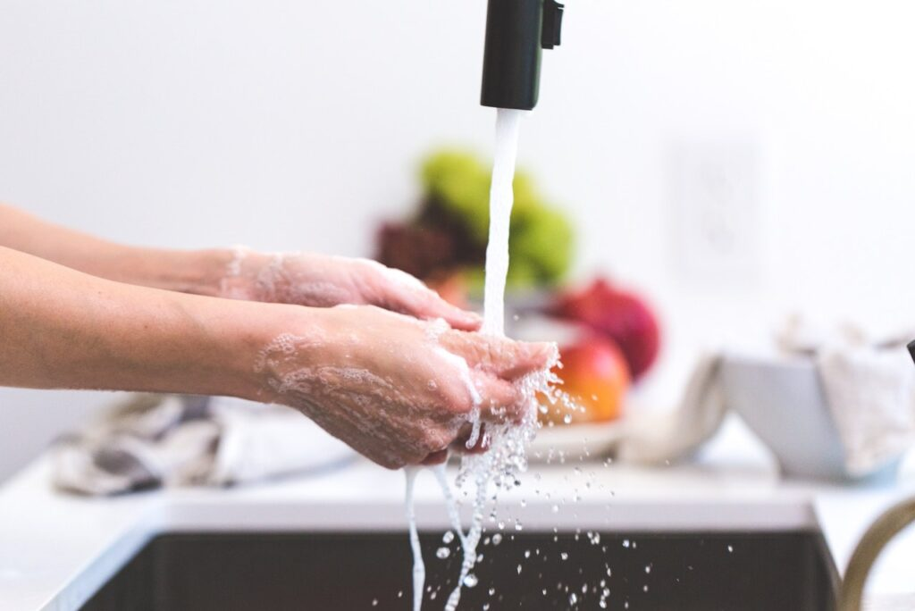 person washing hands in water at kitchen sink