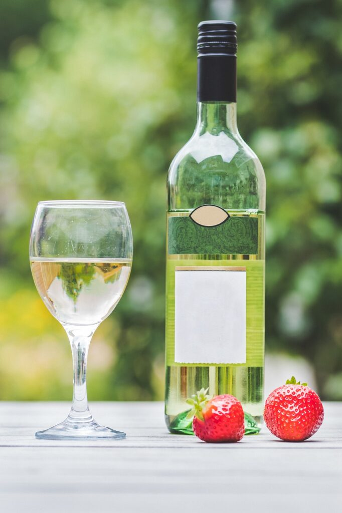 bottle of white wine and glass of wine with strawberries on table