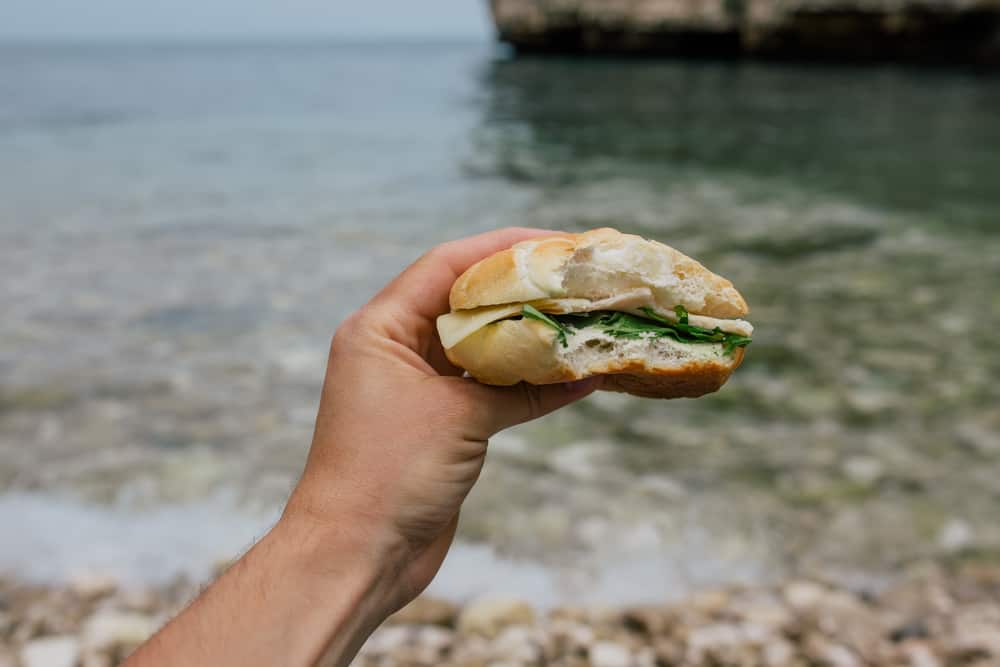 Sandwich in a hand in front of a river
