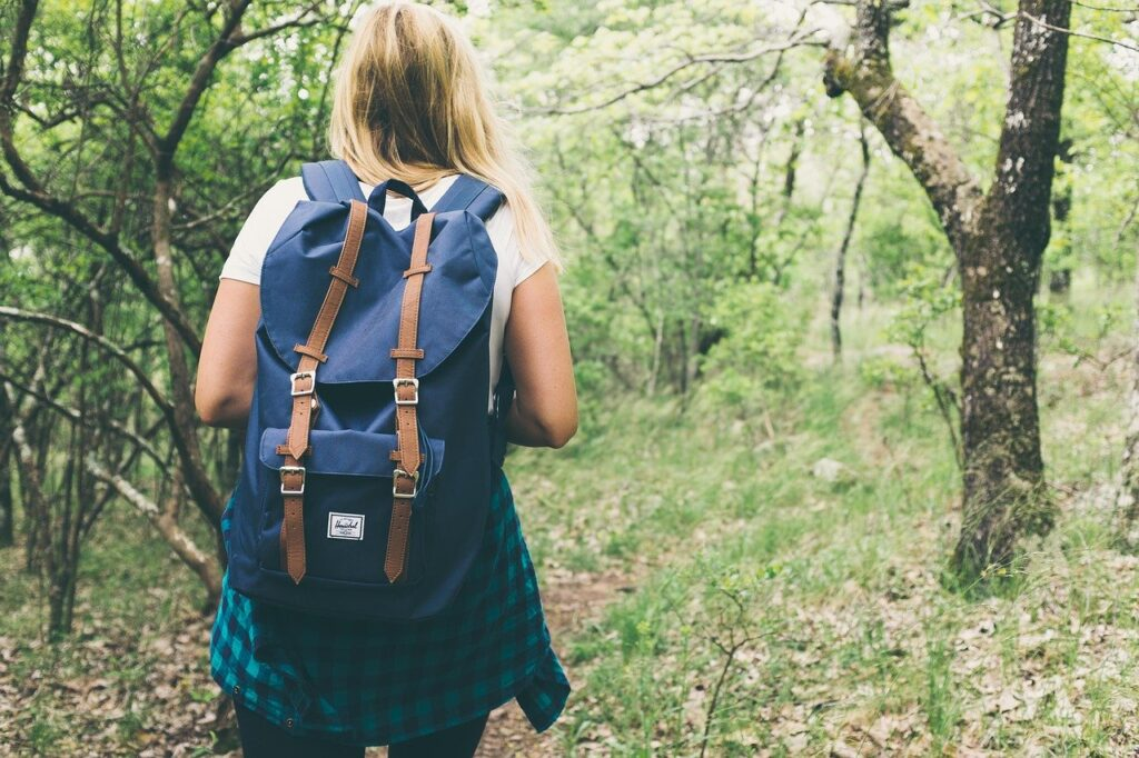 young woman hiking with a backpack on
