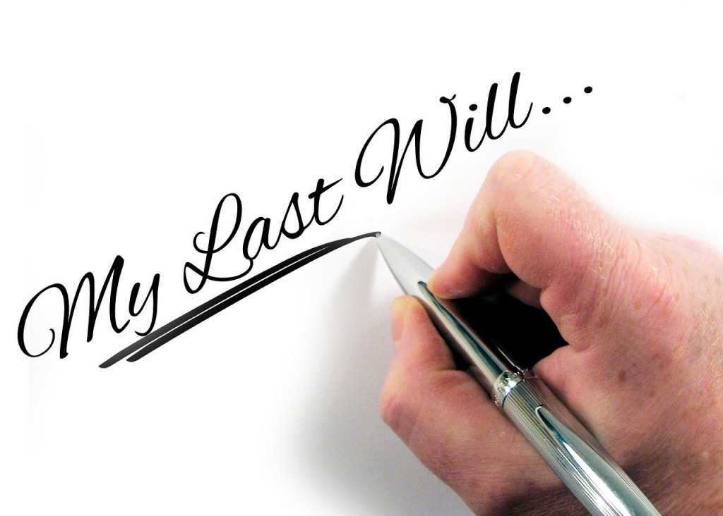 persons hand holding pen with text overlay 'my last will'