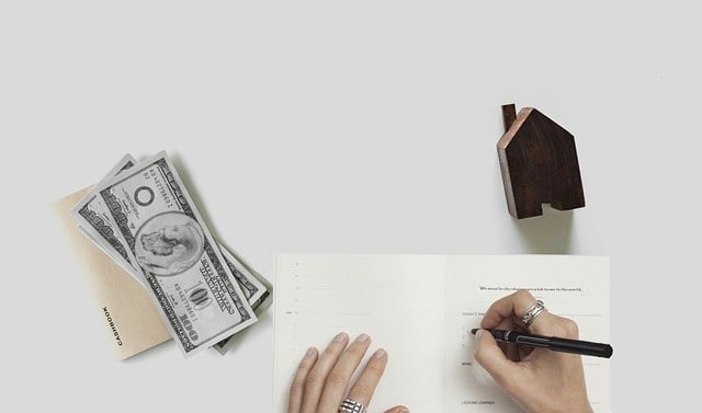 pile of money with person's hand writing in budget document