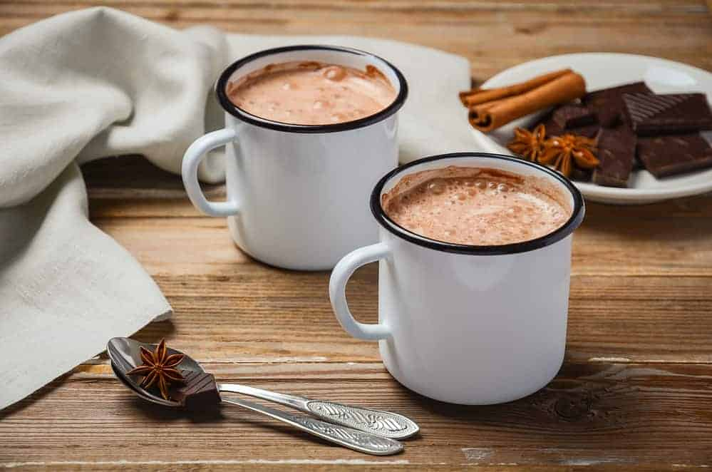 homemade hot chocolate and spices on a wooden table