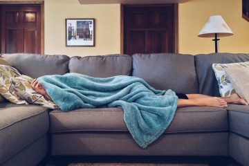 teenager sleeping on couch with blanket