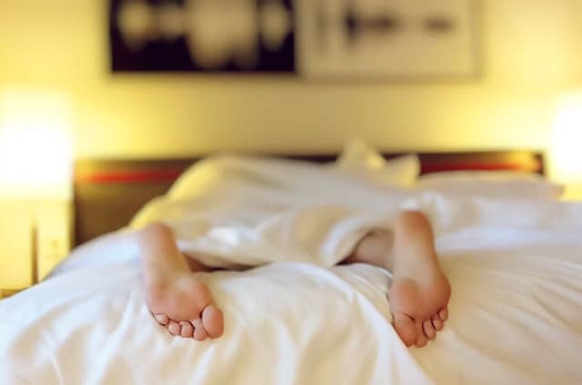 person sleeping in bed with feet hanging out of covers