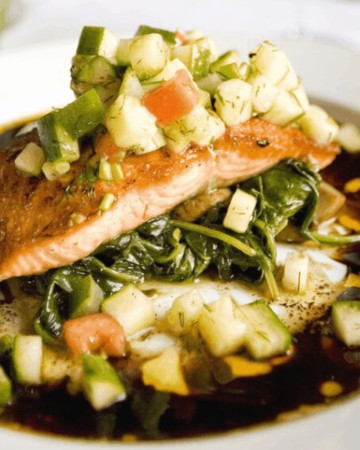 salmon and vegetables on while plate on restaurant table