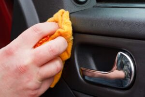 someone Cleaning the car interior with polishing cloth