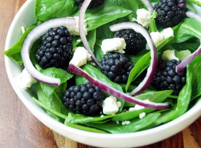 spinach and basil salad with onions and feta in a white bowl