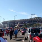 people walk through Candlestick Parking lot to the stadium