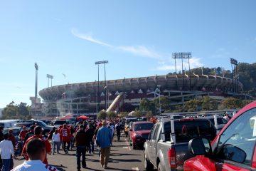 people walk through Candlestick Parking lot to the stadium