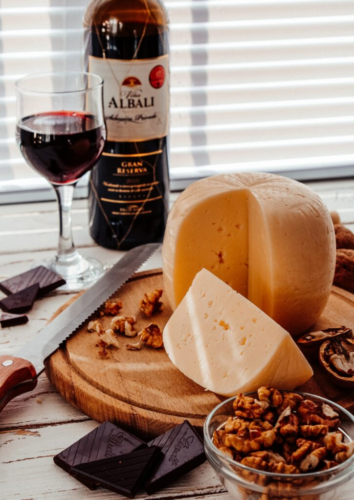 cheese on a cutting board with nuts and red wine in the background