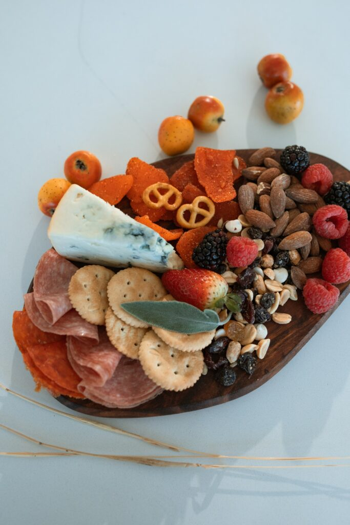 selection of crackers, meat, cheese, nuts and fruit on a wood tray to serve with wine