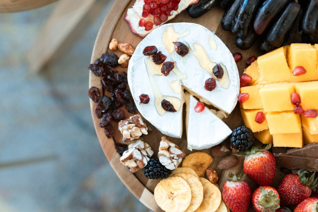 cheese and fruit on a cutting board to serve with wine
