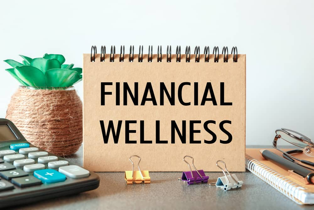 Notebook with the text Financial Wellness on the office table among the stationery.