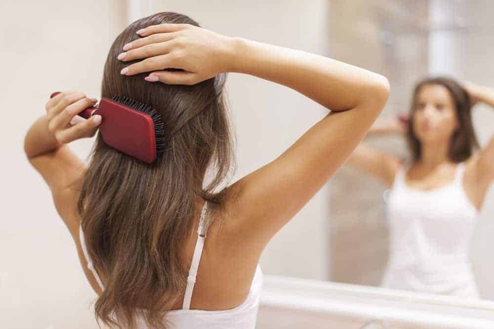 Young woman brushing healthy hair in front of a mirror to reference positive body image in girls