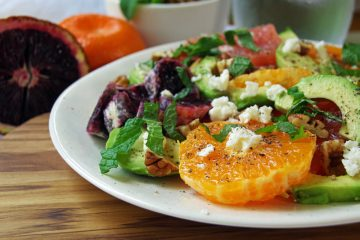 white plate with salad of oranges and avocado