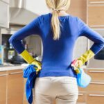 rear view of woman with yellow gloves in kitchen doing housework