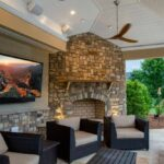 outdoor patio with television, chairs and fire pit