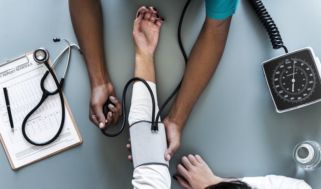 woman getting blood pressure taken at doctor
