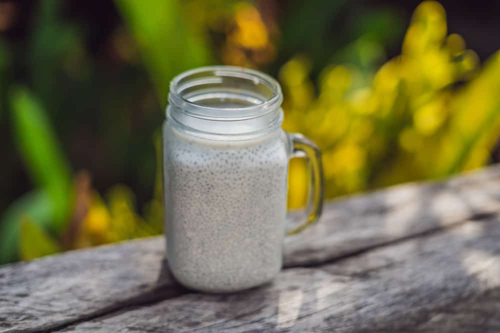 Healthy layered dessert with chia pudding in a mason jar on rustic background.