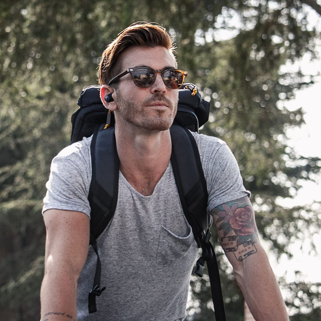 man hiking with backpack on and headphones in ears