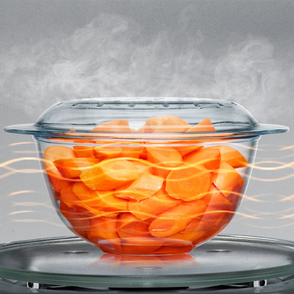 bowl of sliced carrots cooking in the microwave