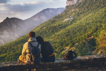 couple sitting on rock wall while hiking in fall