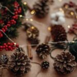 Pine cones, fir branches, wreath, red berries, thread, scissors, cinnamon, cotton, lights on rustic wooden background. Details for making christmas wreath at workshop. Atmospheric image
