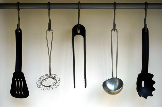 kitchen utensils hanging on wall to create more counter space in kitchen