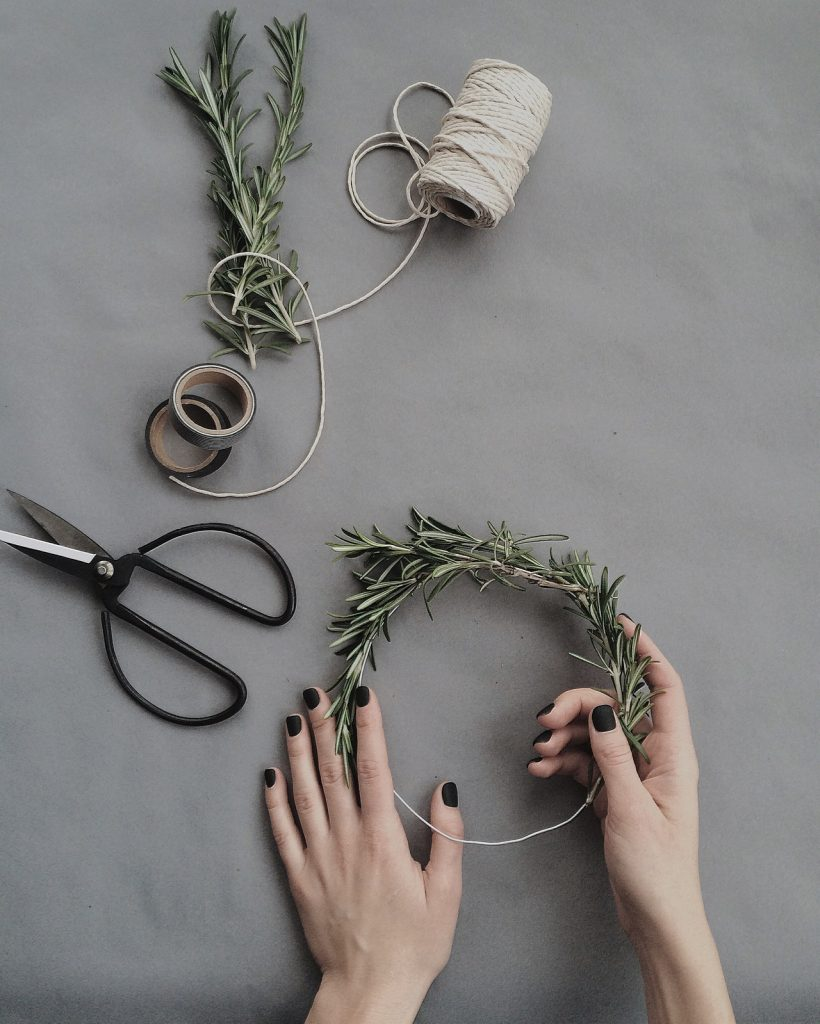 person making natural wreath out of pine branches