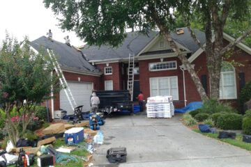 workers doing home maintenance on brick home