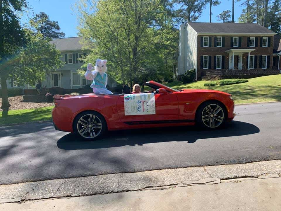 Easter bunny riding in a red car