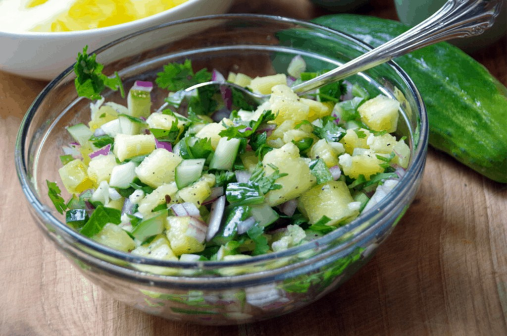 bowl of cucumber salsa with pineapple in glass bowl on cutting board