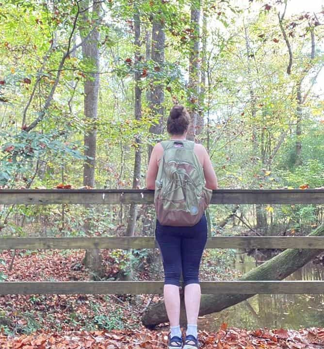photo of woman standing on a bridge in the woods with a back pack
