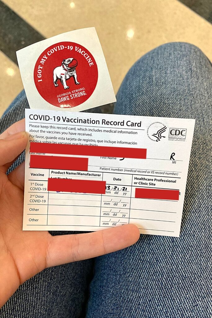 covid vaccination card in a person's hand