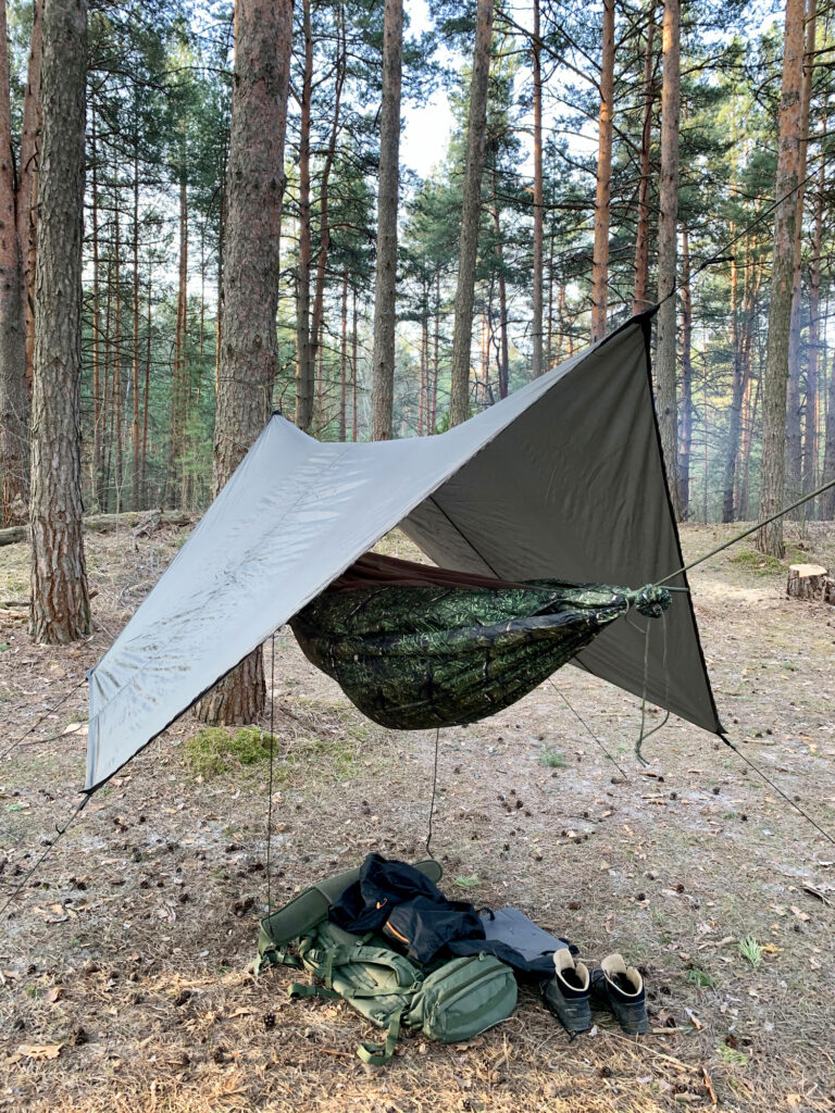 hammock in woods with tarp over it and accessories in pile underneath