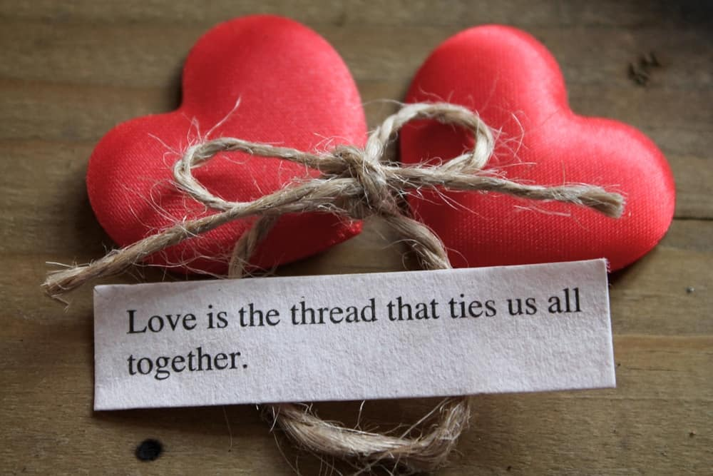 two hearts with string and paper that says love is the thread that ties us all together